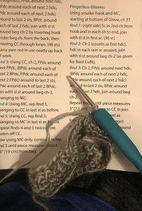 crochet needle atop crochet instructions