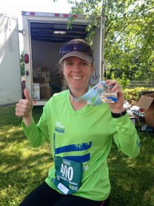 Learn about Coach Mel and how you can complete hold up your medal like she is.