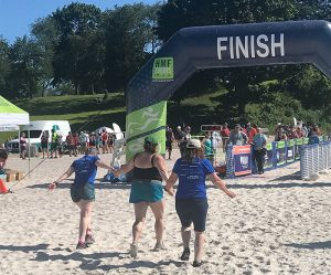 Threesome of women approaching finish line on beach.